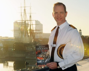 Captain Jerry Kyd, then commanding officer of HMS Ark Royal HMS Victory in background
